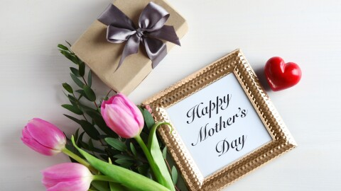 """A """"Happy Mothers' Day message in a frame, next to flowers, a box, and a heart."""
