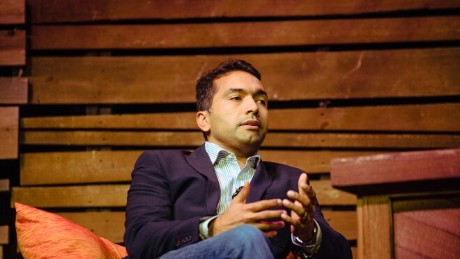 "A man, Maju Kuruvilla, is seated on stage during Amazon ""Live at the Ryman"" event."