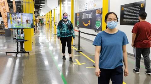 Amazon associates wearing face masks walk along a corridor of a fulfillment center. Behind them, a screen shows visual social distance assistance.