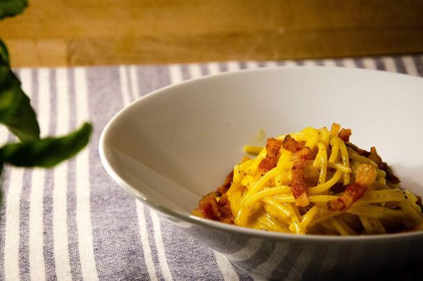 An image of a bowl sitting on a blue and white striped table cloth. The bowl has pasta with bacon inside of it.