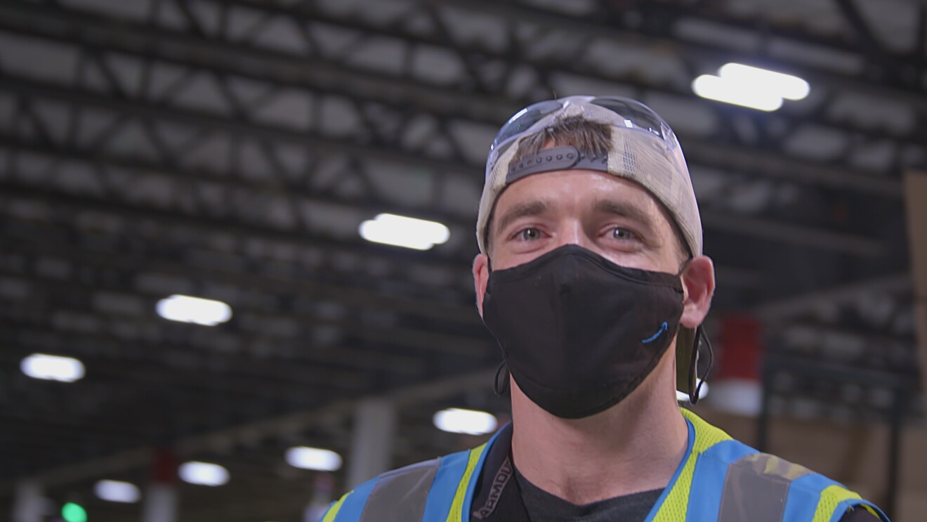 An Amazon employee poses from inside an Amazon Fulfillment Center wearing a backwards cap, black mask, and high visibility vest.