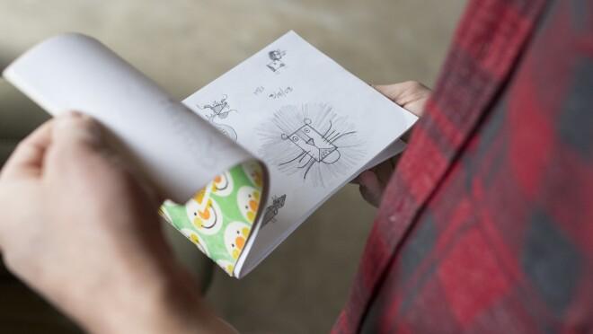 Amazon artist Kyler Martz flips through a sketch book.