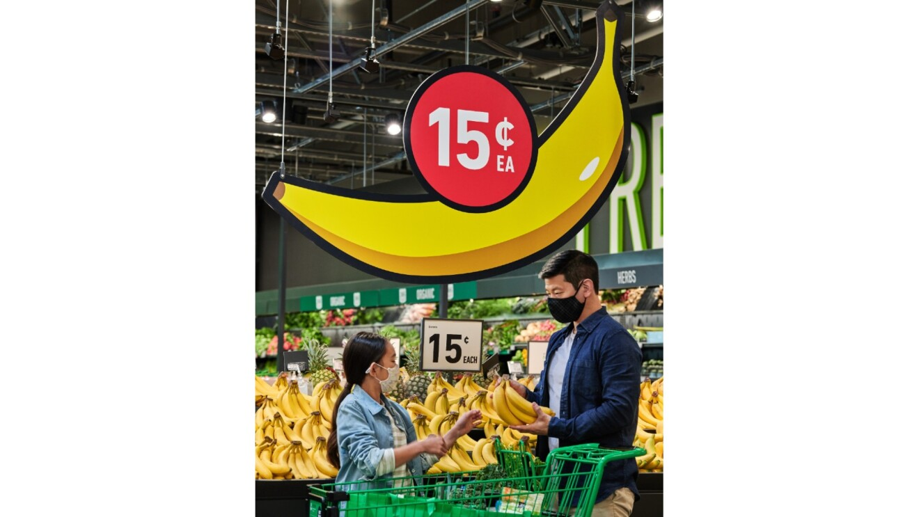 A father and his daughter shop for bananas at Amazon Fresh. Above them is a sign in the shape of  a banana with 15 cents above it.