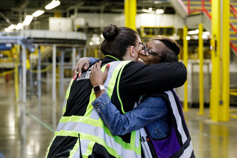 Two female Amazon associates embrace one another in a warm hug. In the background, a fulfillment center / warehouse can be seen.