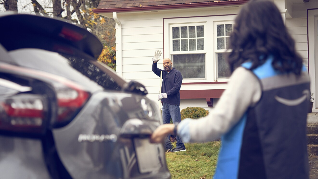 An image of a man waving from his yard. There is a woman wearing an Amazon delivery driver vest opening her trunk and looking back at him