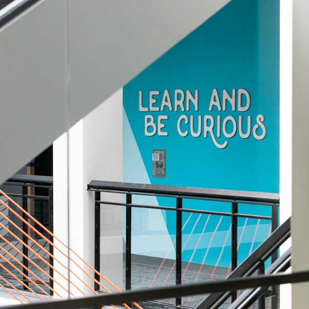 "An office space with a blue wall with the Amazon Leadership Principle ""Learn and be curious"" in raised white letters on a bright blue background."
