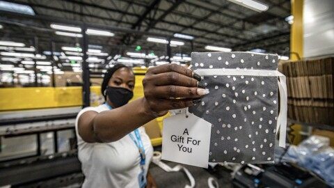 """A woman wearing a face mask working at an Amazon fulfillment center holds up a small gift bag with a tag that says """"A gift for you"""" printed on it."""