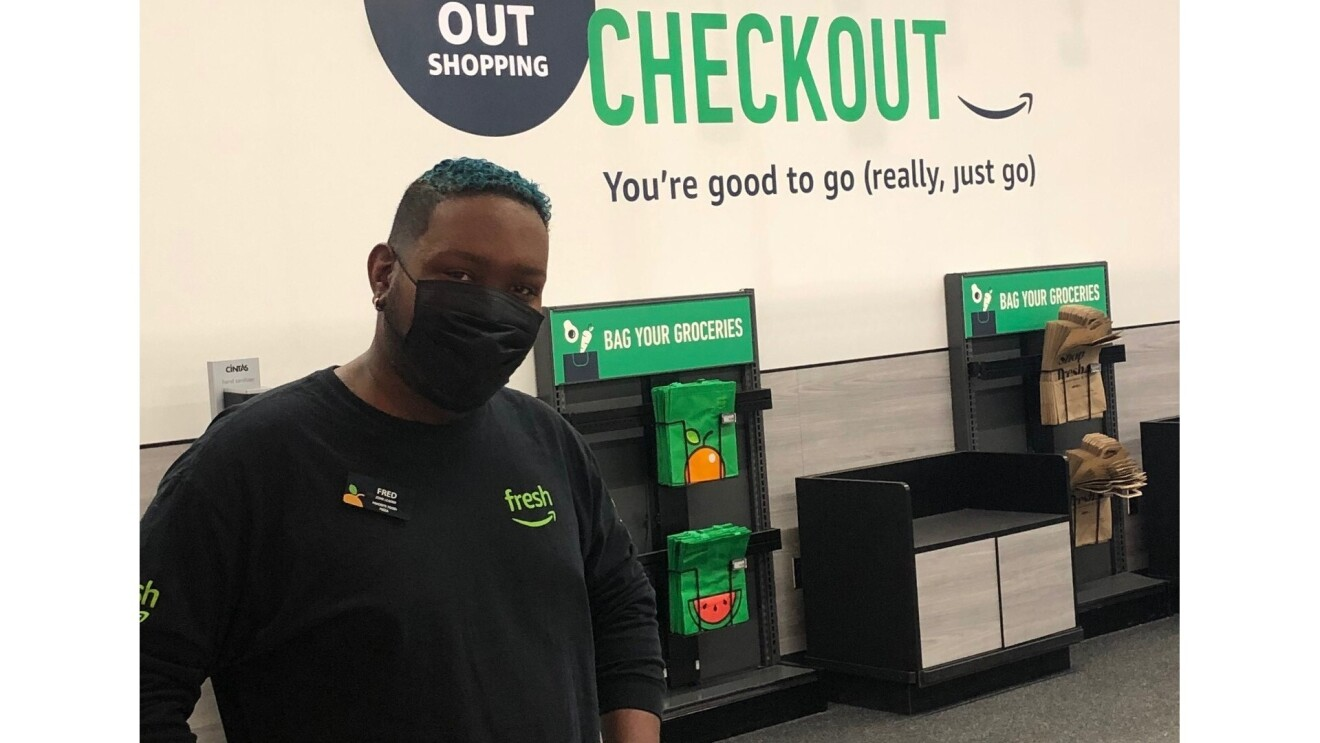 """Fred wears an Amazon Fresh black long-sleeved shirt and a face mask. He poses in front of the Amazon Store where customers can bag their own groceries. The wall above the bags reads, """"You're good to go (really, just go)"""""""