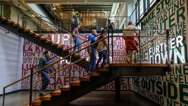 """Amazon employees climb a set of stairs that are decorated with inspirational slogans, like """"try something new""""."""