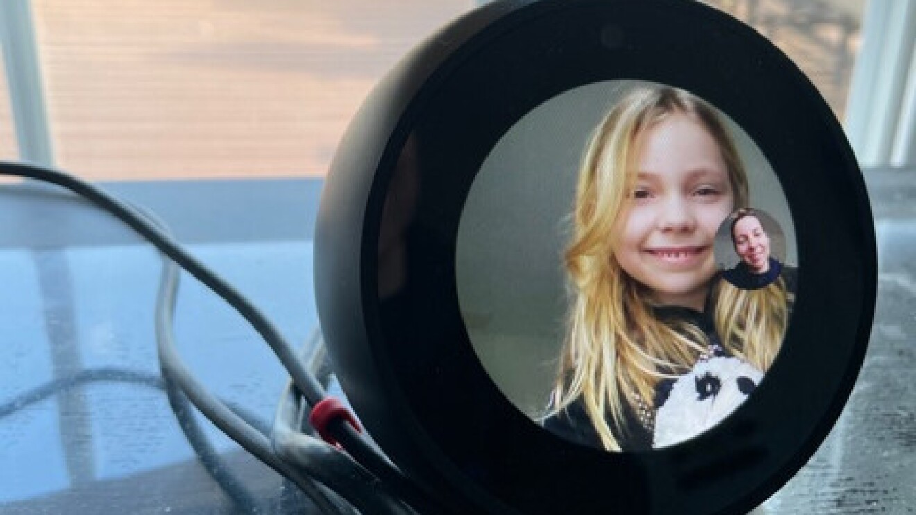 Katelyn is at her desk smiling while her mom, Andi, checks in on her via Echo Spot.