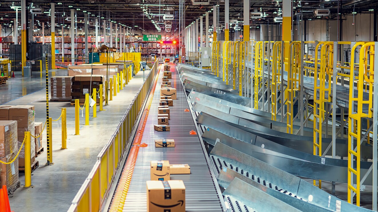A view from inside an Amazon fulfillment center. Boxes ride along a conveyor belt and slide into chutes that guide them to a vehicle for packing and shipping