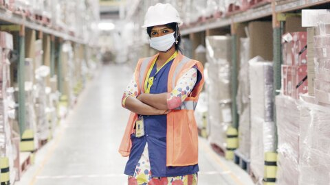 Amazon associate Sathya wears a high visibility vest, a face mask, and a hard hat standing in an Amazon sort center