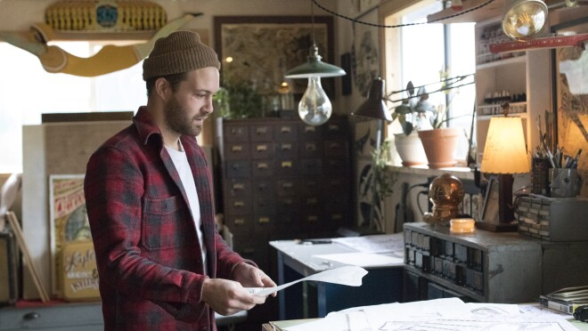 Amazon artist Kyler Martz in his Seattle studio, with a sheaf of drawings on a table.