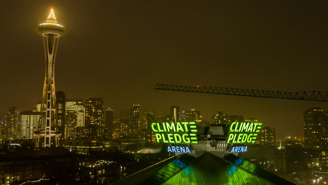 The Climate Pledge Arena signage lit up, with Seattle's Space Needle and skyline showing behind it.