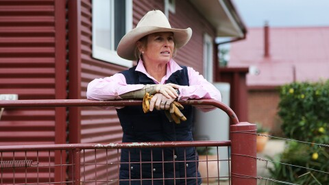An image of a woman wearing a cowboy hat leans on a railing on on the patio in front of her red home, holding her work gloves in one hand and looking off into the distance.