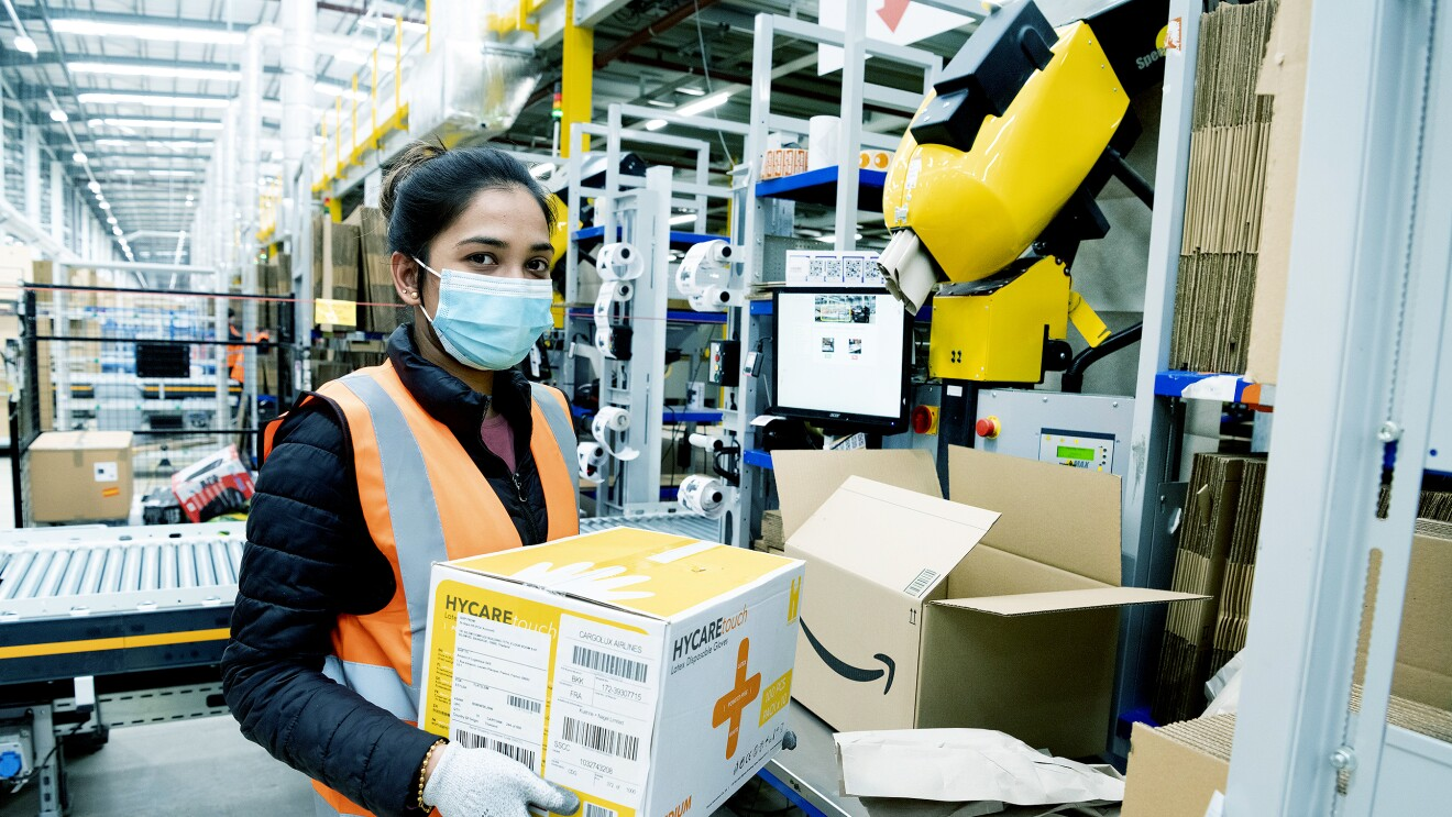 An Amazon fulfilment centre employee packing boxes with medical supplies in the Coalville Fulfilment centre to provide supplies to the relevant government centres. She is wearing protective gloves and a face mask.