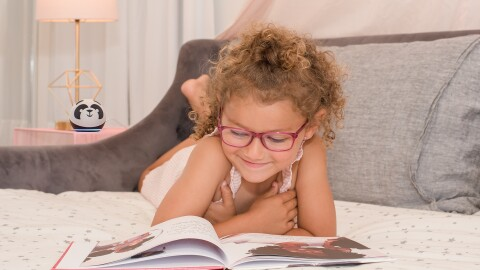 A young girl wearing glasses reads a books in a cozy bedroom setting. Behind her sit an Alexa Echo device and a lamp.