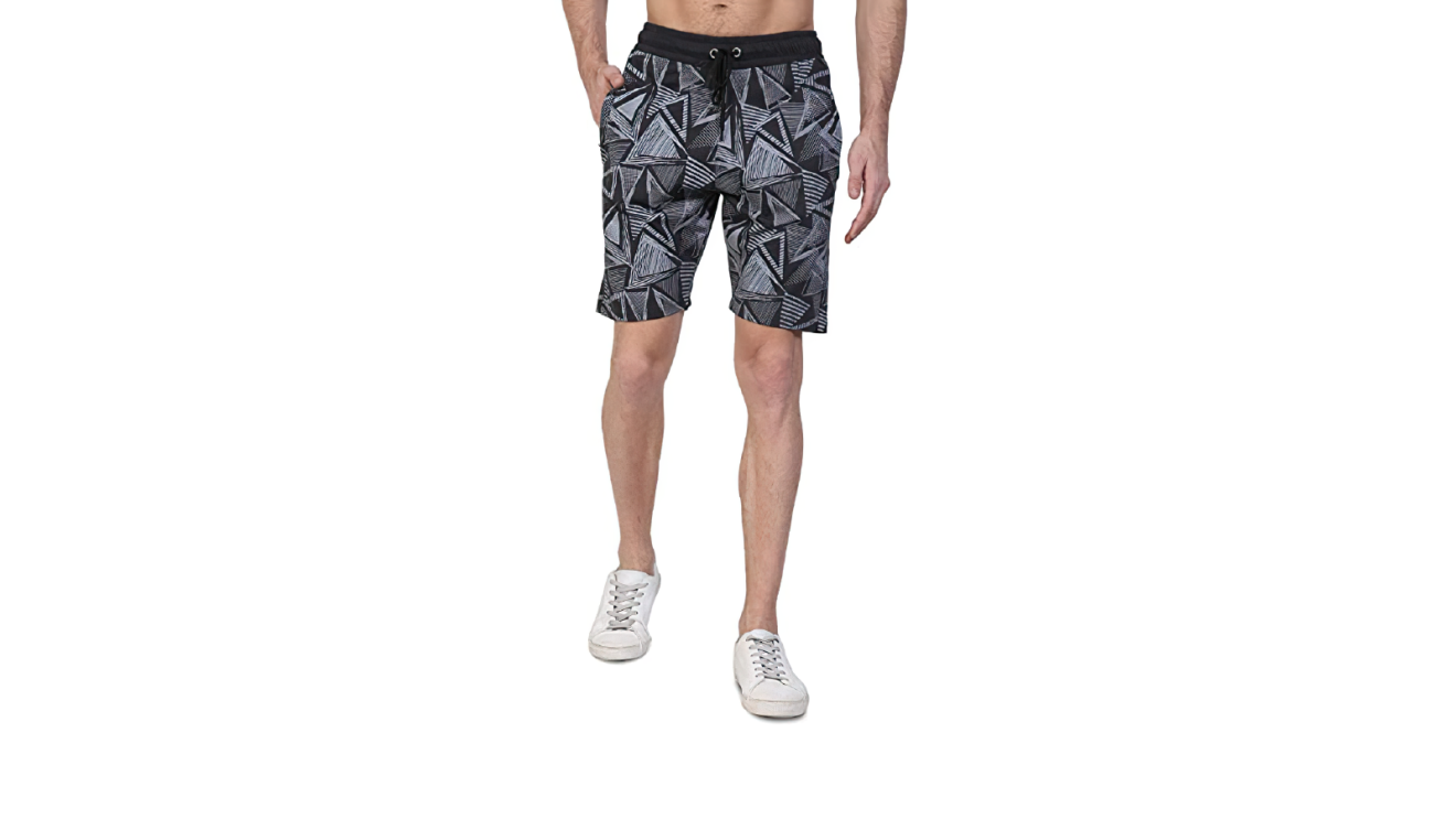 A man is shown from the torso down. He's wearing black geometric knee-length shorts and tennis shoes
