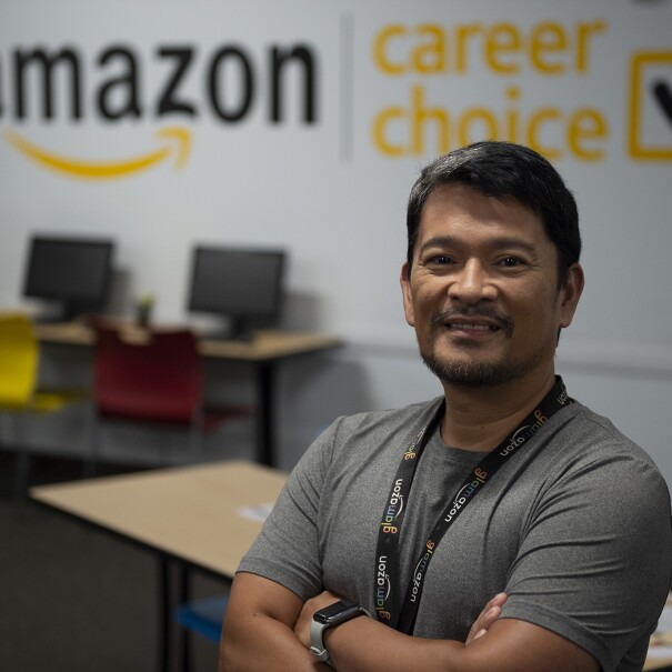 An image of a man smiling for a photo with his arms folded while standing in front of a wall that has the Amazon logo and the Amazon Career Choice logo.
