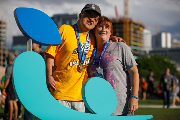 A Special Olympics athlete (male) poses for a photo with a female, behind the USA Games logo.  Part of the Seattle skyline is visible in the background.