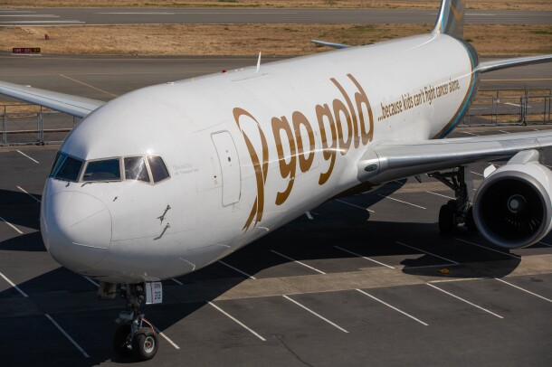 """An Amazon Air plane on the tarmac. On the side, custom messaging that says """"GoGold ...because kids can't fight cancer alone."""""""