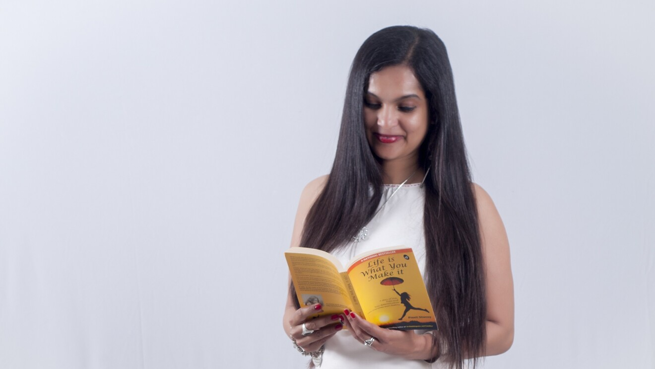 Author Preeti holds a book authored by her and is reading it