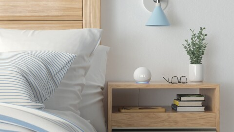 An Echo Dot device sits on a bedside table, displaying 9:03 as the time.