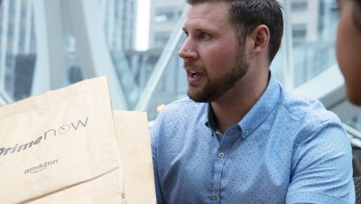 A man holds a Prime Now package.