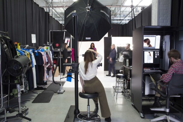 An Amazon Fashion photographer, in a white shirt and brown slacks, photographs a model at Amazon Fashion's studios.