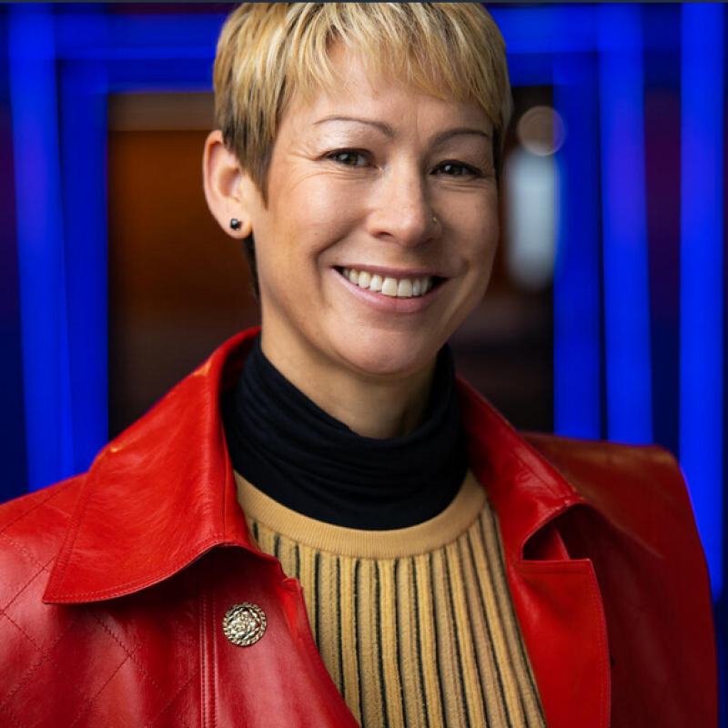 An image of a woman smiling for a headshot in a hallway of blue lights. She is wearing a red jacket and yellow sweater.