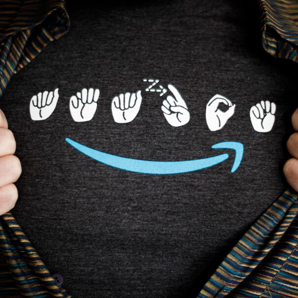 A man wears a t-shirt with the Amazon logo in sign language. Under the signs is a blue Amazon smile. The man is wearing a striped button down shirt over the t-shirt, and is holding the edges of his button down to make the entire logo visible.