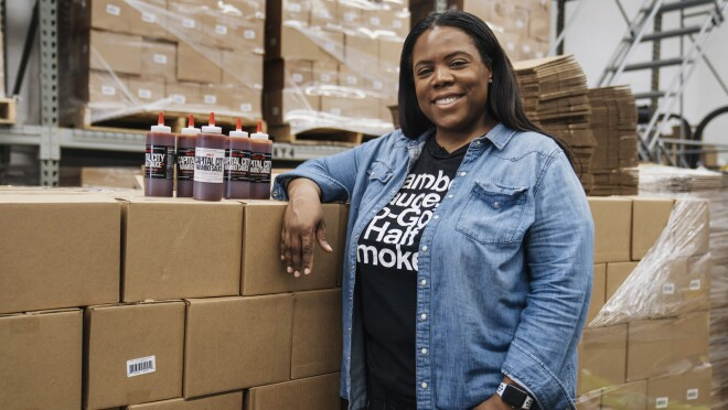 Arsha Jones smiles as she stands in front of stacks of boxes with a handful of Capital City Mambo Sauces next to her on top of the boxes.