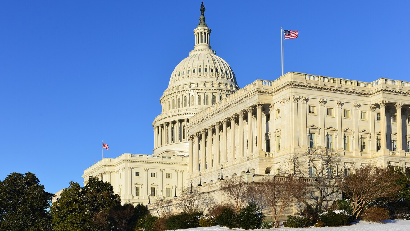 The U.S. Capitol building, on front of a blue sky. In the foreground, snow is on the ground.