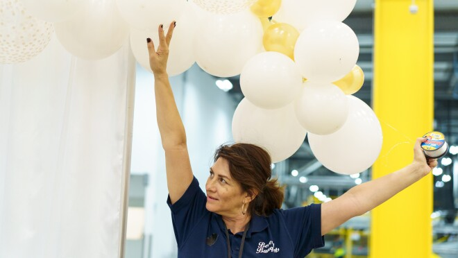A woman holds her arm above her head and lifts decorative balloons.