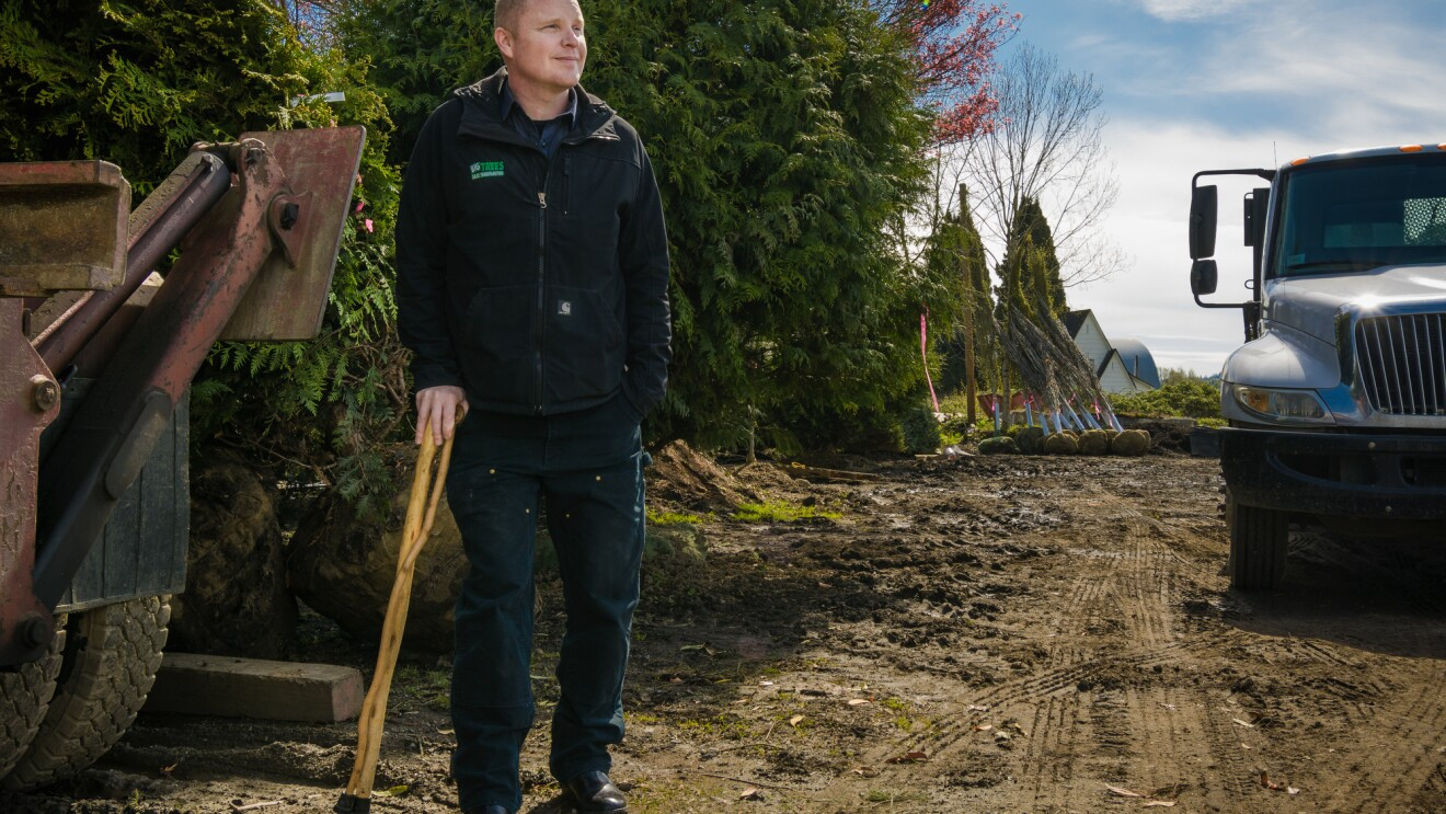 A man stands on a dirt road next to a truck and a bunch of saplings. He is wearing dark pants and a dark jacket that reads Big Trees.