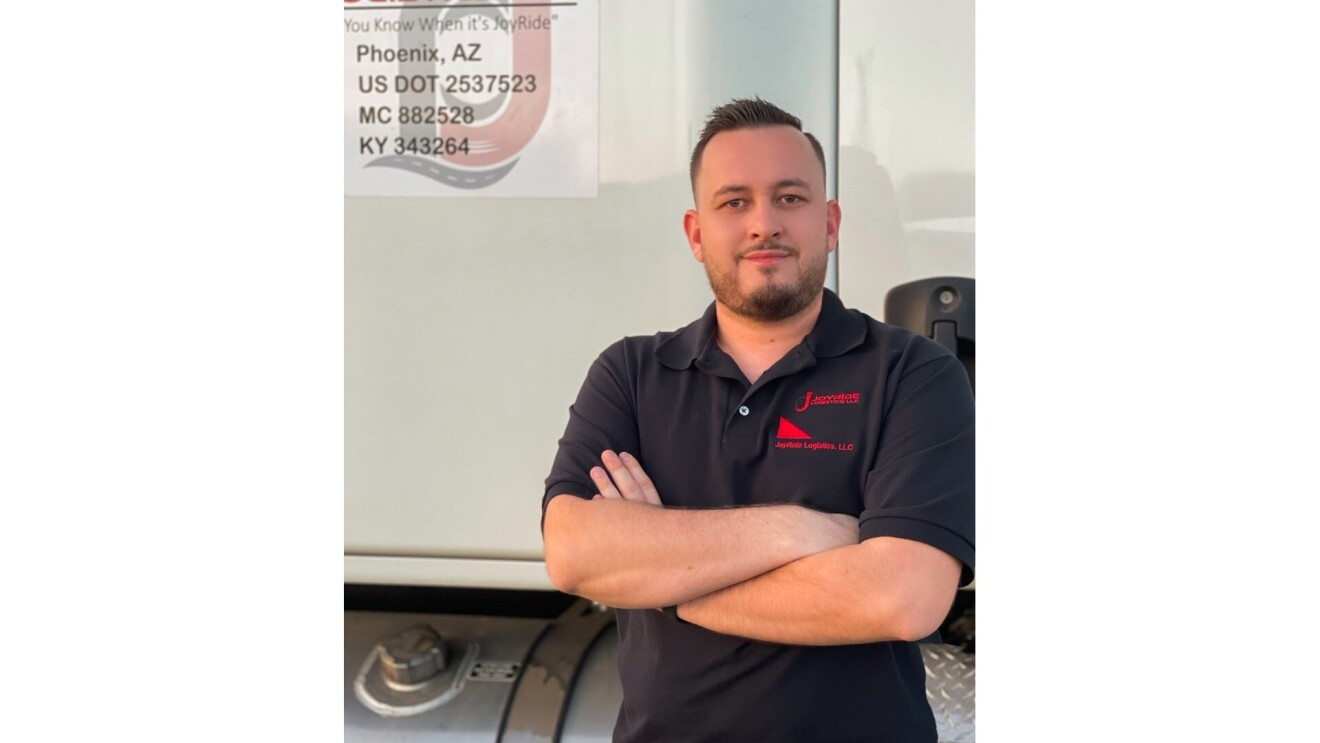 Adis Danan poses for the camera as he stands in front of his semi-truck. He stands with his arms crossed and wears a black collared T-Shirt.