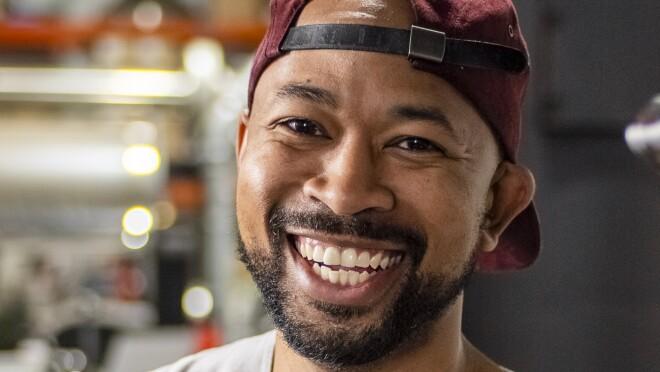 A smiling bearded man in a backwards baseball cap.