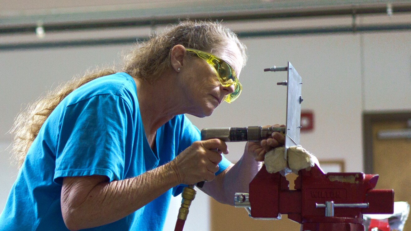 A woman in a blue T-shirt and safety glasses applies a hydraulic tool to a sheet of metal and leans toward a workbench vise.