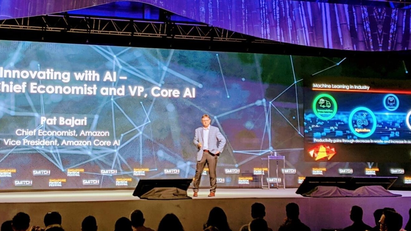 "A man stands on stage at a conference, presenting on ""Innovating with AI"""