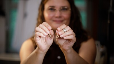 A woman smiles as she holds a pair of earrings towards the camera.