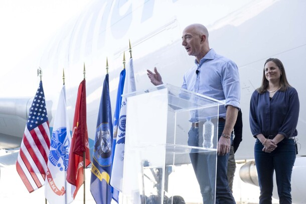 Jeff Bezos stands at a podium in front of the crowd, announcing the newest Amazon Air plane, Valor. Behind him stand Sarah Rhoads and Ardine Williams. The Amazon Air plane is behind them, and to their right are several flags.
