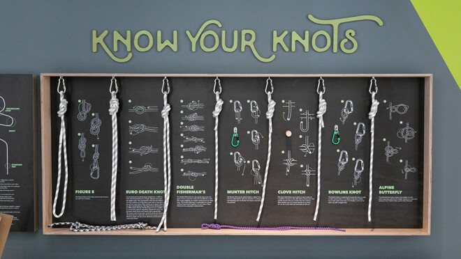 Know your knots signage in the Amazon Boulder office. Knots shown include figure 8, euro death knot, double fisherman's, munter hitch, clove hitch, bowline knot, alpine butterfly.