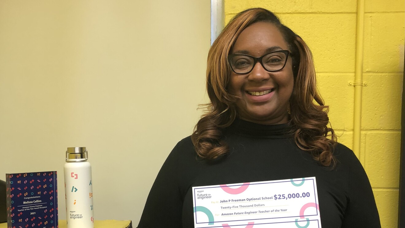 A woman smiles for a photo while holding two checks she earned as an award a recipient of Amazon Future Engineer's Teach of the Year award. One check is for $25,000 and the other is for $5,000.