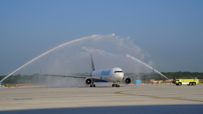 An image of a plane on the runway at the new Air Hub. The plane is being sprayed down with a fluid.