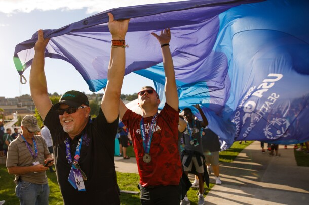 Male athletes seen carrying the ceremonial Special Olympics flag. Athletes are seen holding the flag on the outer edges, while carrying it toward a destination. The athlete in the foreground is smiling while holding the flag with both hands. The second athlete is looking upward while holding onto the flag, while other athletes are seen behind him. The flag extends behind the first two athletes by several feet. Event attendees are watching, in the background.
