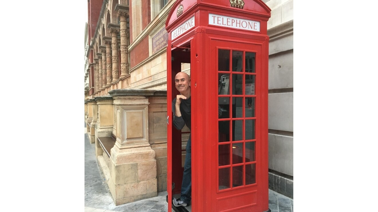Paul posing in a red telephone box in London.