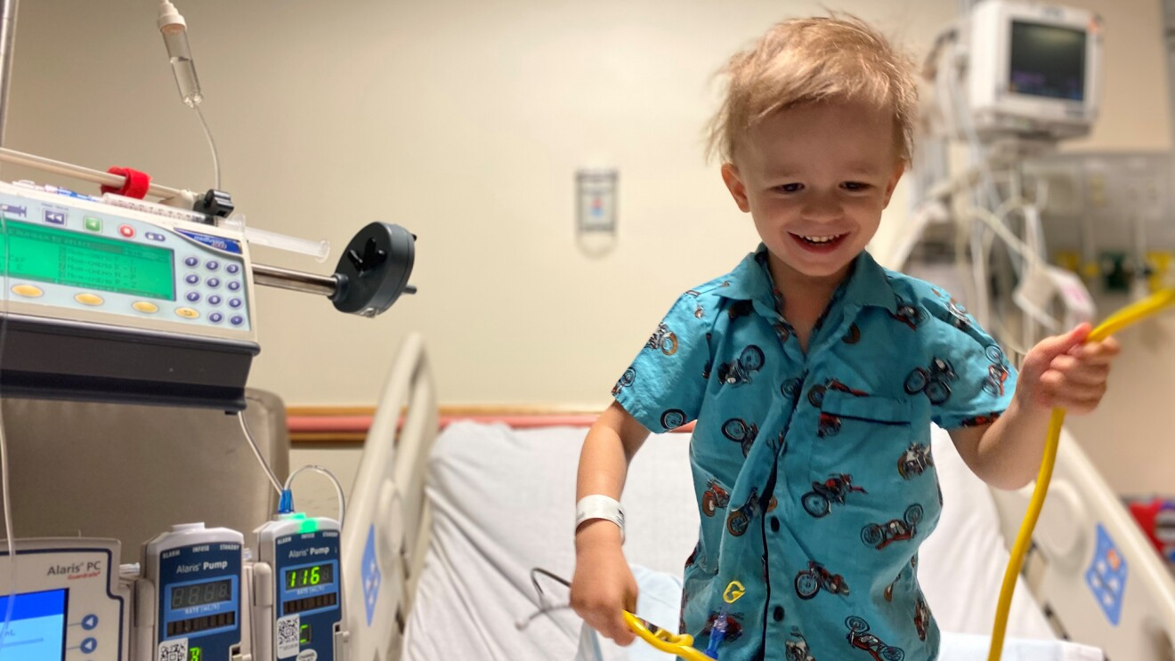 An image of a young boy smiling while standing up on a hospital bed playing with a yellow stethoscope.