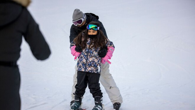 A father helps his young daughter down a ski slope on skis in the wintertime.