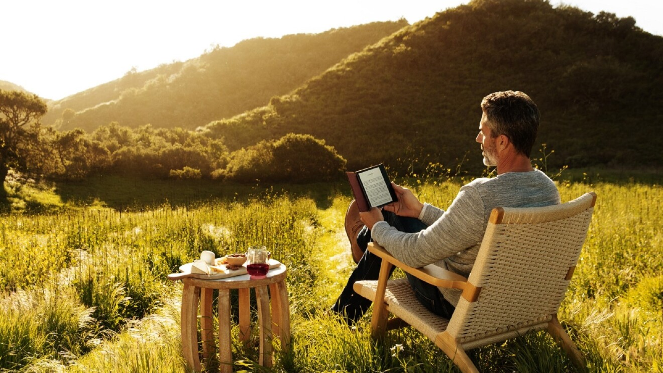 A man reading his all-new Kindle Oasis while looking out at the sun setting over a vineyard