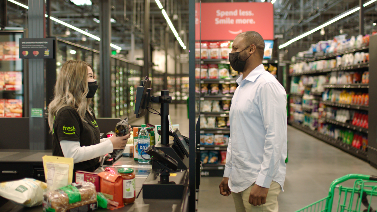 A customer is using the traditional checkout and is interacting with an Amazon Fresh employee as she rings through his groceries.